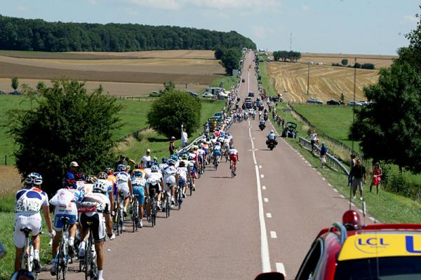 The peloton is stretched out along a long, straight road.