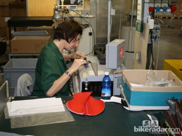 Процесс сварки начинается тут. Работник делает тоньше края ткани в месте склеивания
