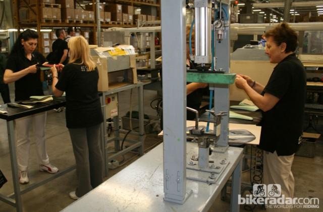 Два рабочих прикрепляют обивку к основе седла